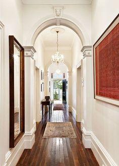 Hardwood floors, white walls, arches