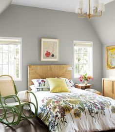 In addition to spending time in the New England farmhouse, the designer also grew up in a 1960s Manhattan high-rise. So a bit of Pop-Art attitude prevents the decor from reading too traditional. This bedroom's bentwood rocker, for example, is painted bright green. In this photo: Both the raffia headboard and the floral bedding came from West Elm. Nickey Kehoe makes the silk-and-linen pillow. Emerson nabbed the caned rocker, still wearing its 1960s paint, at a junk shop. The walls are painted...