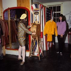Miss Jackie Binder stands in one of the latest 'convict-stripe' fashions while looking at an old fashioned 'What the Butler saw' machine.