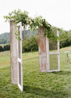 I love this idea for any arch!  Just buy two really old doors and then connect them with a piece of plywood so it will stand and then cover the wood with flowers or babies breath.