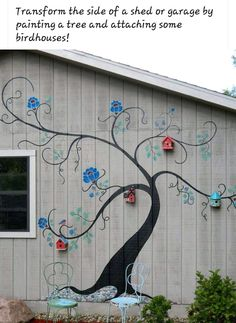 Painted tree and birdhouses on side of building