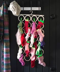 A multi-use hanger is hanging from hooks against a black wood-panelled wall. The multi-use hanger is filled with different coloured socks that are filled with presents.