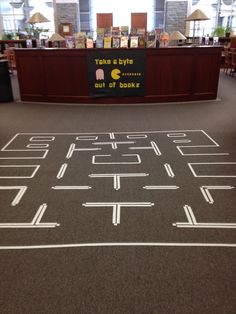 Pac Man has taken over the library for the week, accompanied by a display of fiction and non-fiction books that feature video games. The ideas for this sign and the pac man board on the floor came …