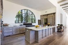 Limed (or white washed) reclaimed wood with marble counters, black range, oiled bronze hardware. Great look! Home in Tennessee by Austin Bryant Moore