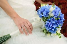 Blue bouquet of flowers with long stems, tied with a white ribbon to match a beautiful white wedding dress.