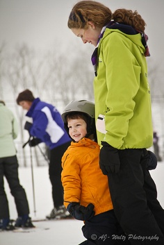 A child learning how to snowboard.  Waltz Photography.