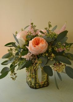Arrangement for a tea party themed bridal shower. Vintage tea canister with peach rose and eucalyptus.