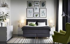 A bedroom furnished with a dark grey divan bed combined with white chest of drawers and bedside tables. Shown together with a moss-green wing chair.