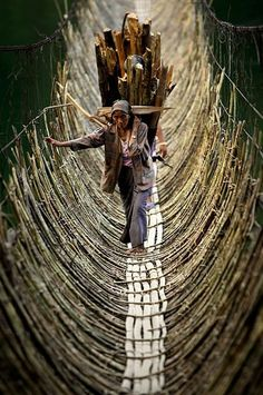 Porters crossing a bridge, Himalaya.