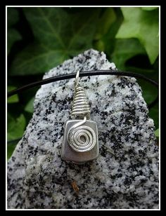 Vintage and slightly used rock climbing stopper has been repurposed as a pendant hung on a leather cord.