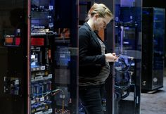 An IBM product manager stands in front of an IBM z13 mainframe server at the CeBIT trade fair in Hanover.