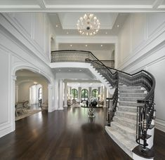 Grand staircase of luxury mansions with double height foyer, custom ironwork railing details, paneled walls, cathedral ceiling and decorative chandelier Mansion Interior, Dream House Interior, Dream Home Design, Home Interior Design, House Design, Ikea Interior, Foyer Staircase, Staircase Design, Chandelier Staircase