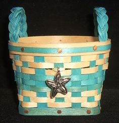 """Our 2020 Sand & Sea Basket is made of Maple in Natural & Aqua Weave that is square at the bottom, round at the top and features braided handles and a Starfish Tie-On.   Measures 3"""" in diameter at the top and is 2"""" tall  (measurements may vary and do not include braided handles).   $30.00    $30.00"""