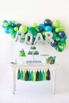 Dinosaur children's birthday party dessert table inspiration. Green and blue decor featuring balloons and tassels. T-Rex/Dinosaur Party styling by Happy Wish Company. Photography by Tammy Hughes Photography. Stationery by Minted artist, Patricia Wallace.
