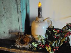 Old Jug...with a lighted taper...greens & berries.