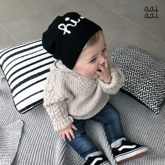 This tiny tyke is cozy and cute in jeans worn with a snuggly sweater, beanie and cool shoes.