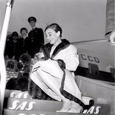 Audrey wears a coat by Dior and Mr.Famous during their arrival at the 'Ciampino' airport, Rome, January 1958