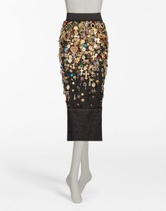<i>The Spring-Summer 2017 is a journey towards an imaginary Italian Tropic, where the icons traditionally associated with Italy, like bread, pasta and good luck charms are merged with a holiday atmosphere, punctuated by cocktails, ice cream and sequins.</i><br><br>Jacquard pencil skirt with contrasting colored topstitching and flounce, embellished by a cascade of appliqué details and pins: <br>• High-waisted with a wide stretch waistband<br>• Central ...