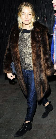 Sienna Miller wore a boxy blouse and baggy jeans with a luxe fur coat