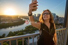 Happy smiling young business woman with hand raised holding a smart phone takes a selfie against panoramic view of Lady Bird Lake and the Austin, Texas Cityscape during vibrant golden sunset.