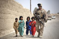 Afghan children walk alongside U.S. Marine Lance Cpl. Jacob Kartchner, a team leader with 4th Platoon, Kilo Company, 3rd Battalion, 3rd Marine Regiment, and 28-year-old native of Long Beach, Calif., in the hopes of receiving candy from Kartchner as he patrols with fellow Marines and Afghan National Police outside the Hazar Joft Bazaar here, April 8, 2012. (DVIDS photo by Cpl. Reece Lodder. Used with permission.)
