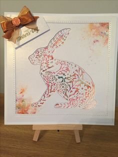 Sizzix rabbit cut out of centura pearl card, piece of card coloured with pixie powders then both the card with aperture & die cut rabbit stuck over the pixie powder background. Sprinkled pixie powders in the corners, put a frame around, finished of with a sentiment & a bow with a gem