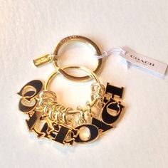 """NWT. COACH KEYCHAIN Beautiful and Classy!!!  """"C""""O""""A""""C""""H""""  lettered keychain. Gold tone with black letters.  Gorgeous!!! Coach Accessories Key & Card Holders"""