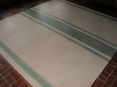 I have been painting floorcloths for many years now. I have painted several in the faux grainsack style. This one is painted in linen and shades of