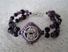 This beautiful bracelet has black glass beads, purple faceted beads, sterling silver plated bead caps, seed beads, purple diamond shaped frame with pewter silver pentacle. 7 long. Toggle clasp.