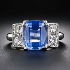 A stunning and sophisticated original Art Deco ring, crafted in     platinum, circa 1930, and featuring a bright cornflower blue Ceylon     sapphire weighing just under four carats.  The colorful gemstone is guarded left and right by a pair of glistening  old-mine cushion-cut diamonds, all four weighing .60 carats total. French  import marks.