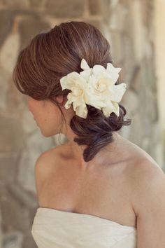 with a veil tucked underneath the flower?