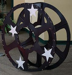 Our Lighted Hollywood Reel features a large black movie reel with silver star accents and is accented with white string lights. Lighted Hollywood Reel measures 3 feet 10 1/2 inches