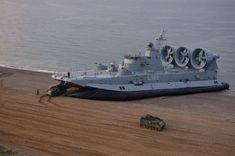 Greek Zubr-class hovercraft discharging M113 APCs onto a beach