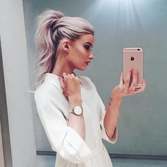 Pastel pale pink hair color trend. Girl with pink hair taking a selfie.