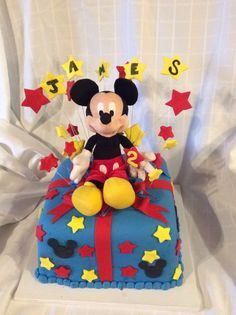 "3 (10""x2"") square layers stacked, frosted in vanilla buttercream, covered in fondant and gum paste decor, plush Mickey Mouse"
