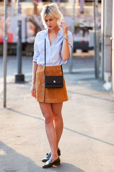 Linda Tol com look em street style com saia botões e camisa.