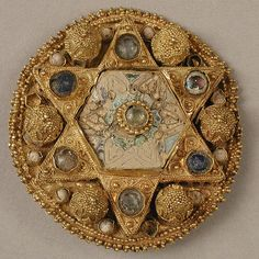 "Brooch, 970–1030  Ottonian (probably northern Italy)  Gold with pearls, glass, and cloisonné enamel.  Decorated with miniature architectural forms.  1.5"" in diameter."