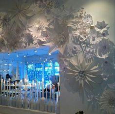 Paper flowers decorate the wall at a wedding.