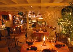 A photograph of the intimate garden terrace at Coyaba Restaurant, Grace Bay, Providenciales (Provo), Turks and Caicos Islands.