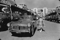 A woman watches a parade of different Fiat models driven around the test track of Fiat's Mirafiori plant in Turin, Italy.