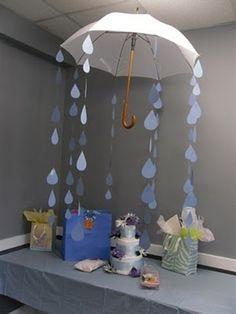 Mesa de regalos para baby shower decorada con paraguas adornado con guirnaldas. #DecoracionBabyShower