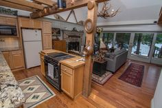 We love this Deep Creek Lake home's layout!! With unique interior decorations and features, it gives this adorable home a casually rustic feel and the perfect lake vibe. The arbor top of the kitchen allows for an open feeling while subtly separating the rooms. So cute!