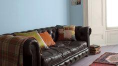 Las paredes azules levantan el ánimo en esta confortable sala de estar.