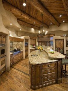 Large kitchen in Southwest home with log beam ceiling with two-level kitchen island that blends into the entire room's design