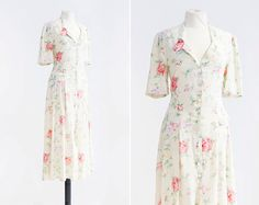 A beautiful home sewn 1940s vintage dress. This piece features a romantic watercolored print, short sleeves, a jewel neckline with a shirt collar and