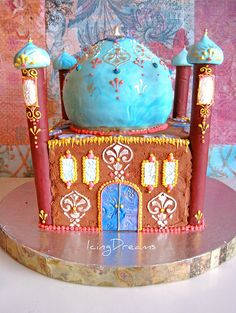 """Eid Mosque Cake    Tricky cake to make but i enjoyed making this. Turned out to be a pretty fancy mosque too! I used a basic 8"""" Chocolate buttercream covered square cake with a 6"""" for the dome which i carved a little to get the right shape. I had made my own fondant for the dome with Marshmallow fondant and decorated it stencils and piping details.  Happy Eid to all that celebrated, I hope it brought happiness with family and friends =)"""