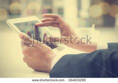 Close-up of Indian male hands touching digital tablet, formal businessman with cup of coffee on table.