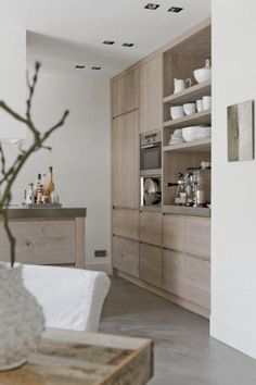 pale blond wood contemporary kitchen - floor to ceiling cupboards and built-in appliances in stainless steel: