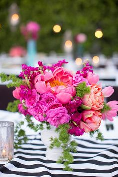 For a fun, preppy reception, pair a bright, coral-pink centerpiece of peonies, roses, and funky greenery with a bold black-and-white-striped table linen. I love this look for a summer wedding or any outdoor event.