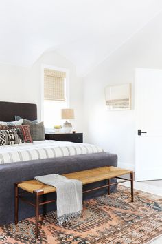 A bright yet gray bedroom with patterned pillows